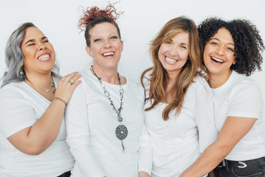 four women wearing white smiling