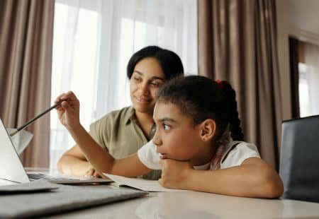 Single mother helping her child at computer with distance learning